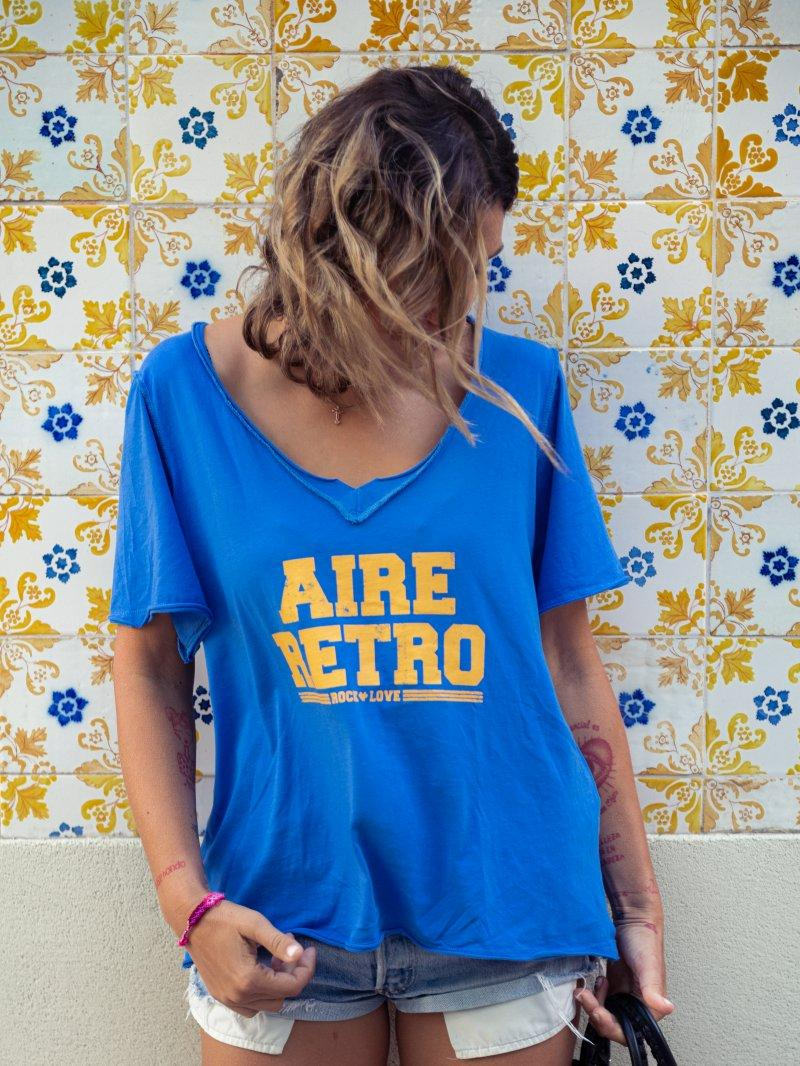 Camiseta teñido azul con costuras vistas, escote en pico y serigrafía en pecho.